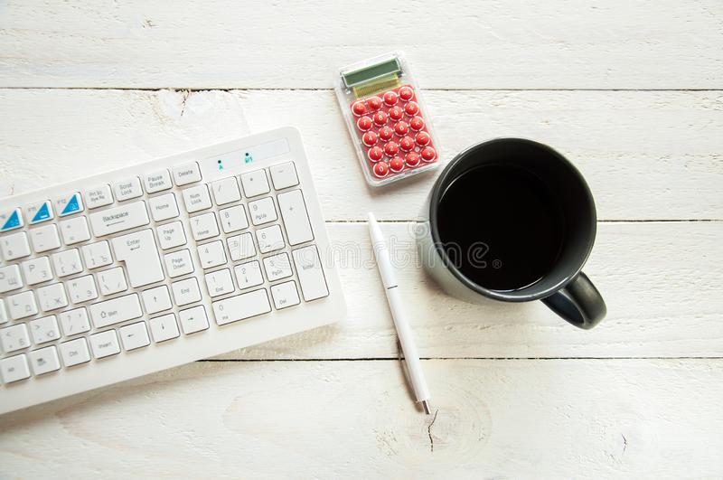Black cup with coffee and computer keyboard on a white table. White wooden background. stock photo