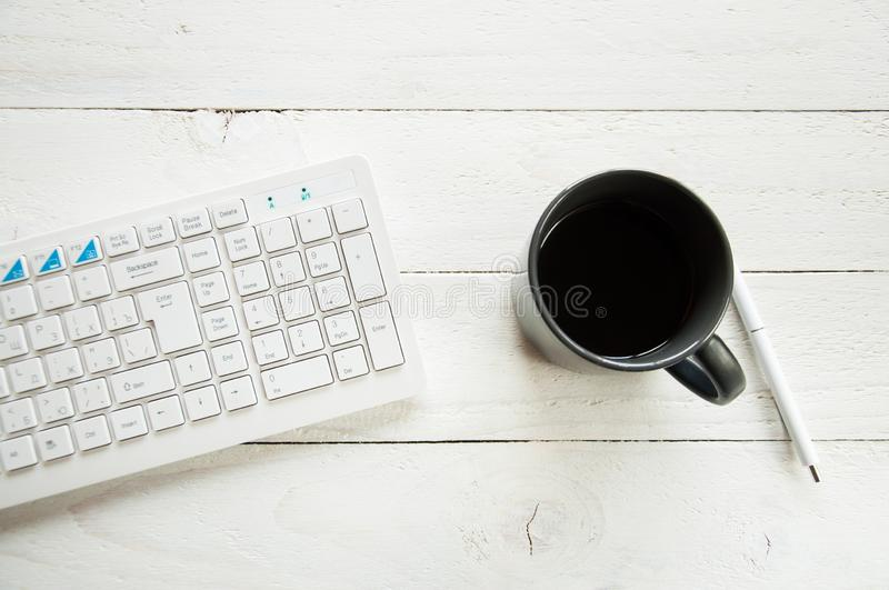 Black cup with coffee and computer keyboard on a white table. White wooden background. stock image