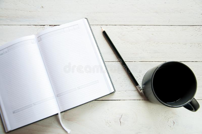 A black cup with coffee and an open notebook on a white table. White wooden background. stock photo