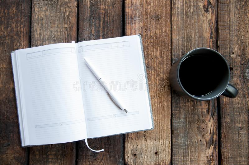 Black cup with coffee and open notepad on a wooden table. Brown wooden background. Board royalty free stock photography