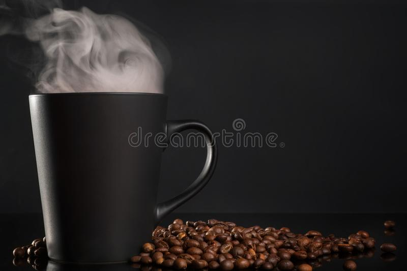 Black cup of coffee with steam on black. Black cup of coffee with steam and coffee beans on black table royalty free stock photo