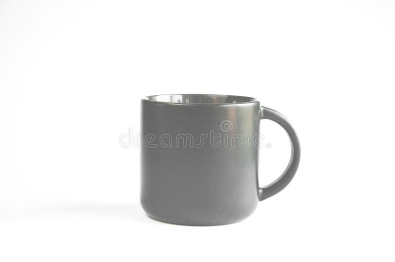 A black cup with coffee or tea stands on a table on a white royalty free stock photography