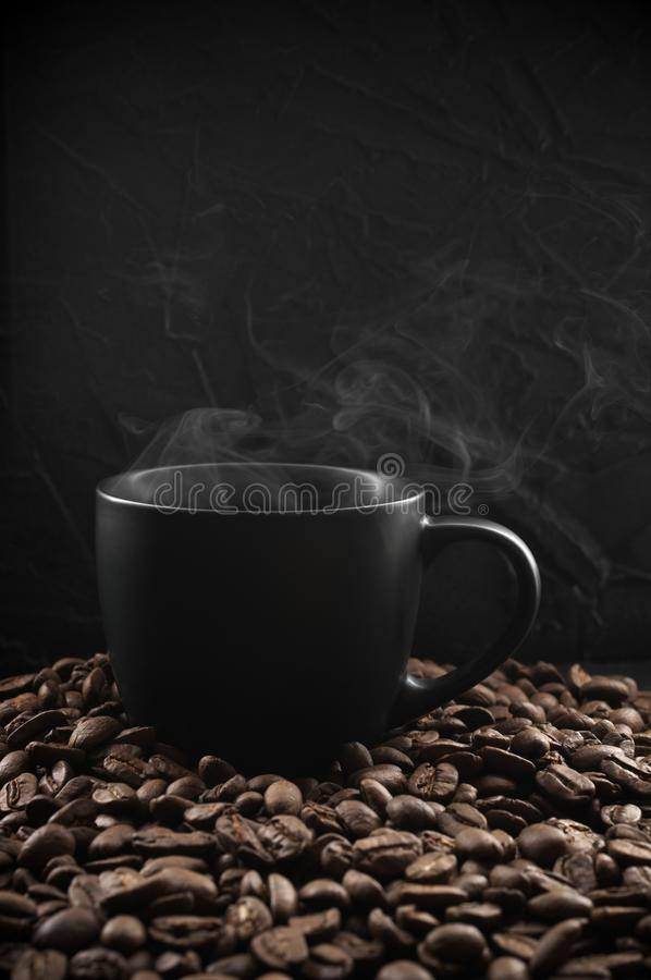 Black cup of hot coffee. With steam in coffee beans on dark background stock photos