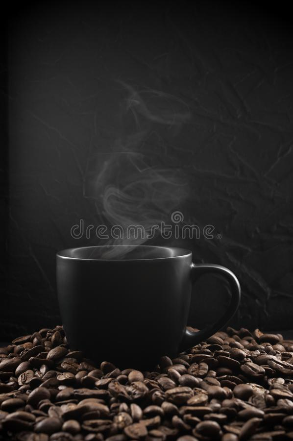 Black cup of hot coffee. With steam in coffee beans on dark background royalty free stock photos