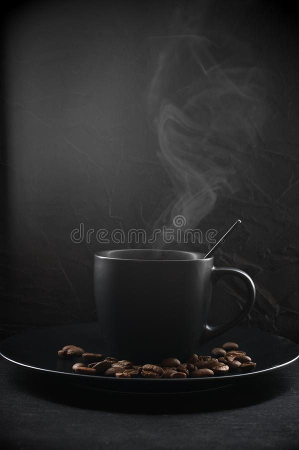 Black cup of hot coffee. With steam and coffee beans in plate on dark background royalty free stock image