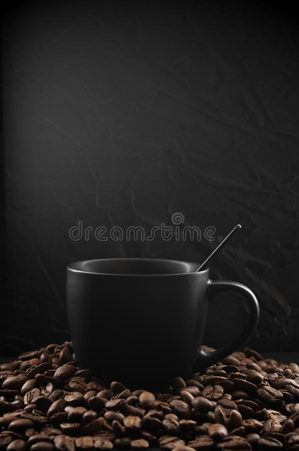 Black cup of hot coffee. With steam in coffee beans on dark background royalty free stock image