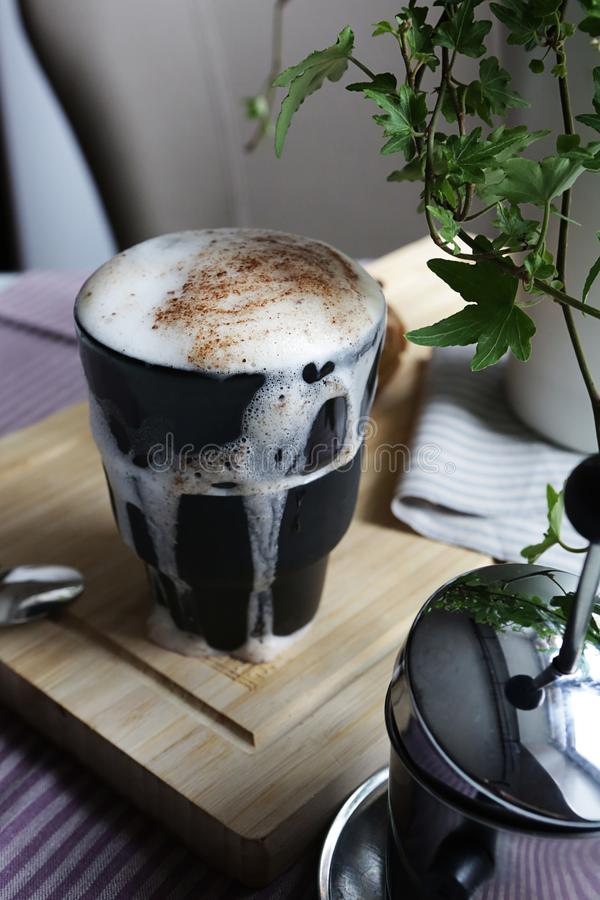 Black cup overfilled with coffee, with milk foam flowing down outside the cup stock images