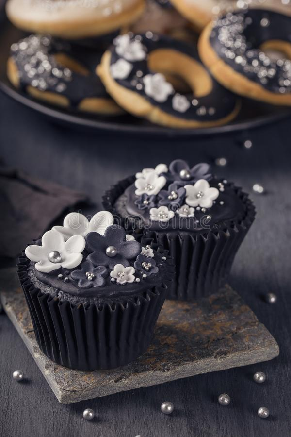 Black cupcake on a wooden background royalty free stock photography