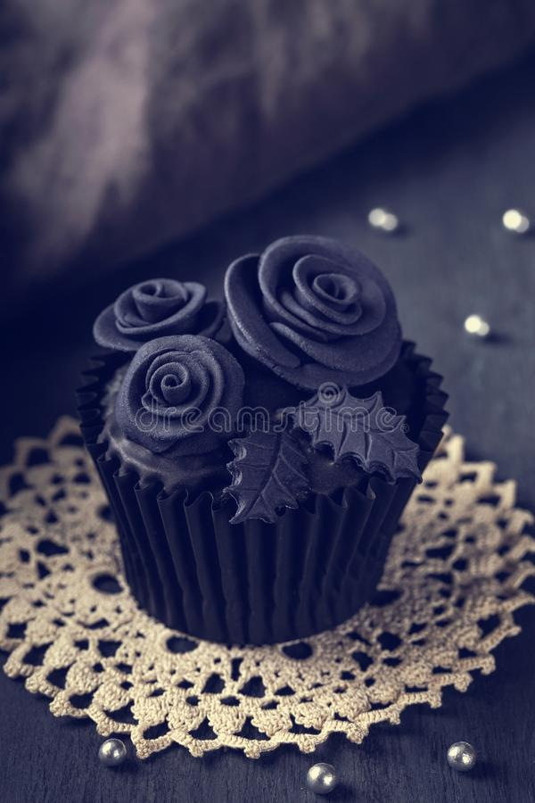 Black cupcakes on a wooden background stock photography