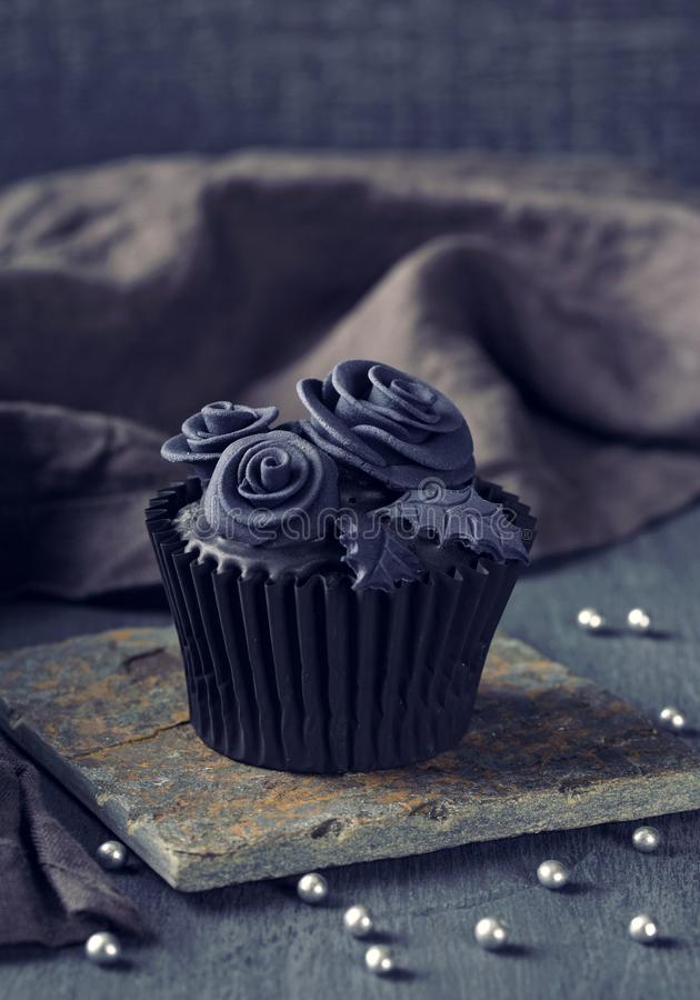 Black cupcakes on a wooden background stock photos