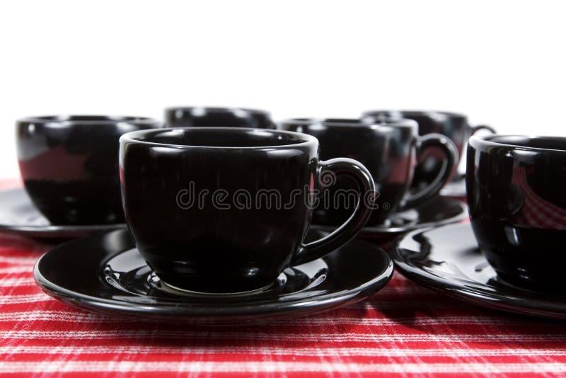 black cups demitassesaucers arkivfoto