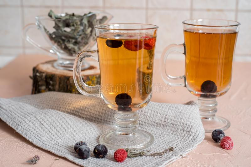 black currant tea with green leaves in a glass Cup in the autumn on the background of a window with raindrops on a white wooden royalty free stock photos