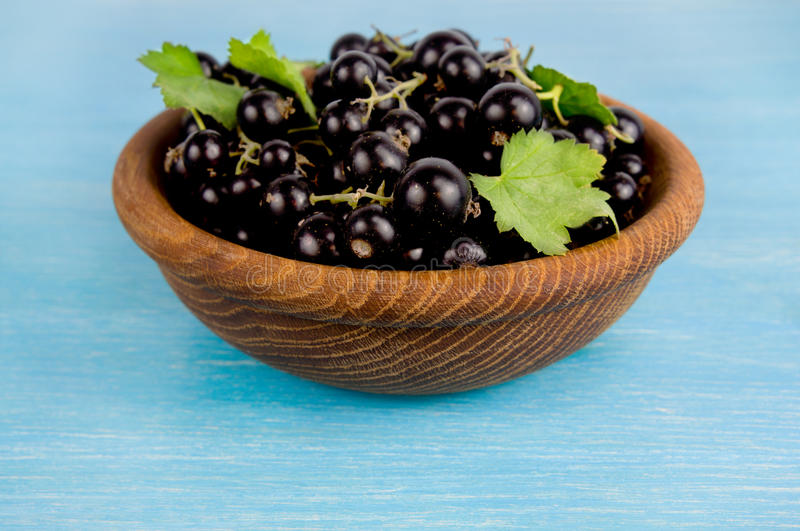 Black currant in a wooden bowl. royalty free stock photography