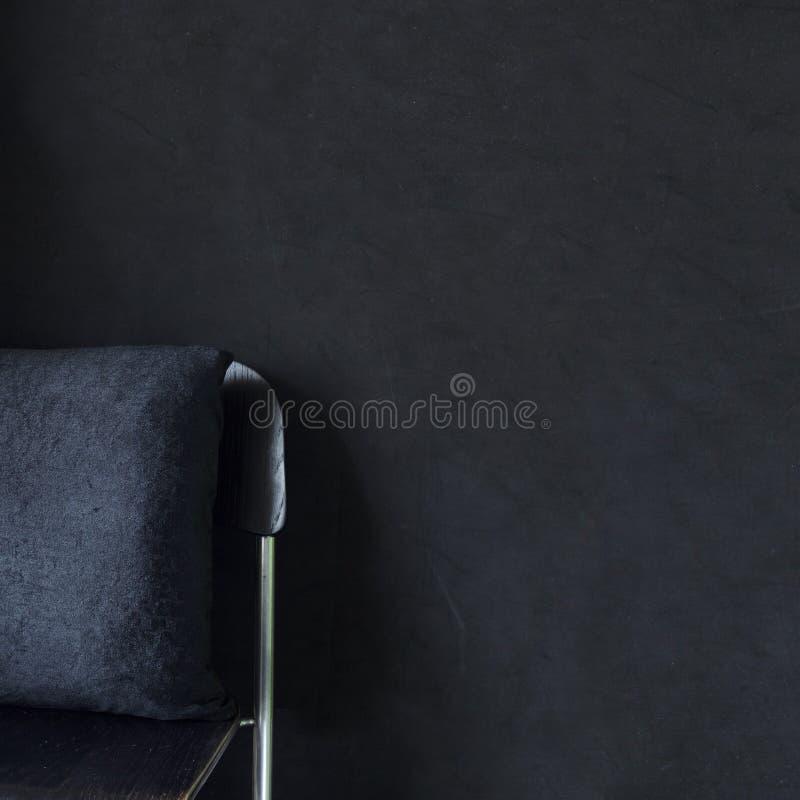 Black cushion on stool in black bedroom interior royalty free stock photos