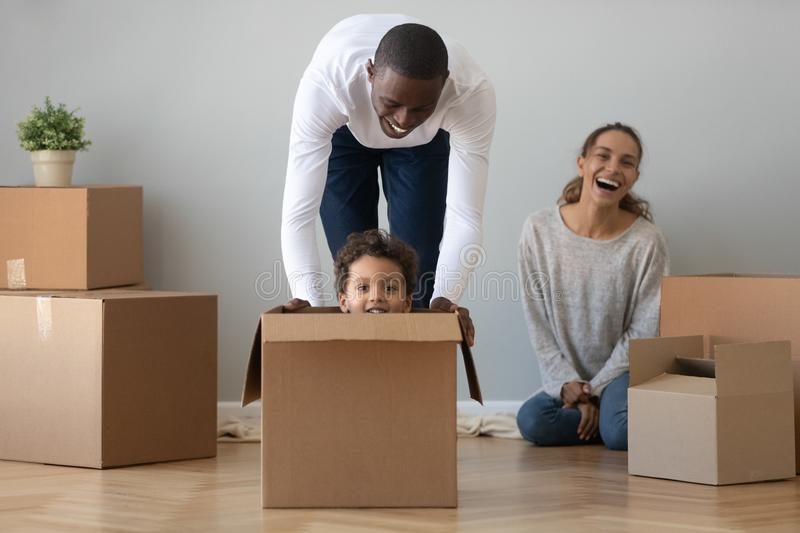 Black dad playing riding son in box on moving day royalty free stock photo