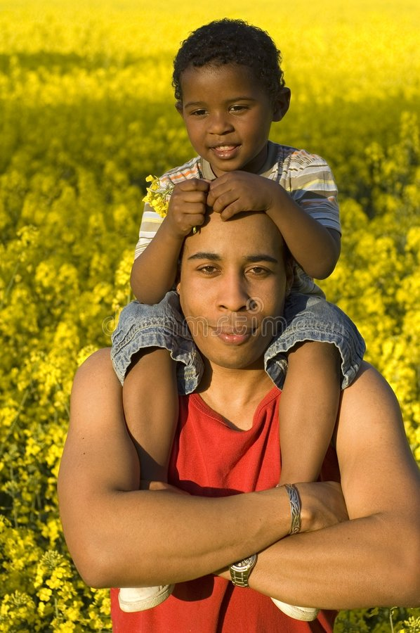Black dad with son. Father with his son on his shoulders