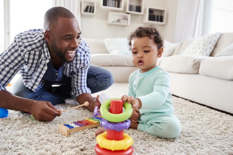 Black dad and toddler son playing on floor at home, close up stock photo
