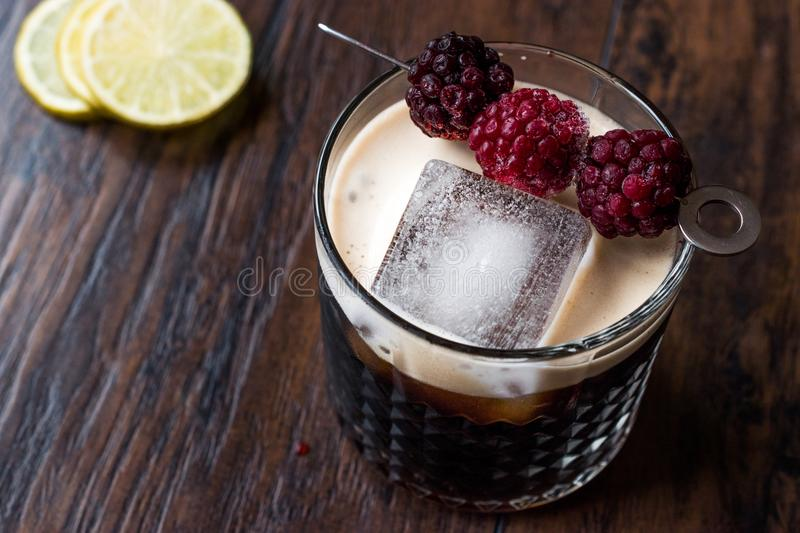 Black / Dark Beer Cocktail with Blackberries and Ice on Wooden Surface. Beverage Concept stock image