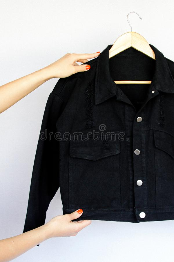 Black denim jacket on a hanger and women`s hands with a red manicure on an  background. stock photos