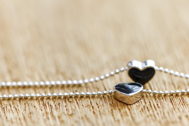 Black diamond heart shape locket pendant with necklace. On wooden background royalty free stock photo