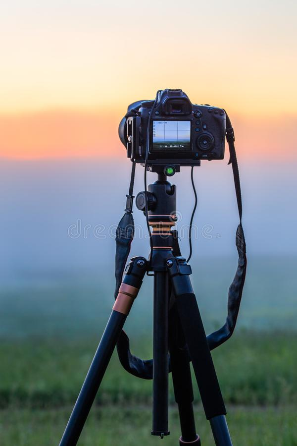 Black digital camera on tripod shooting foggy morning landscape at summer with selective focus royalty free stock photo