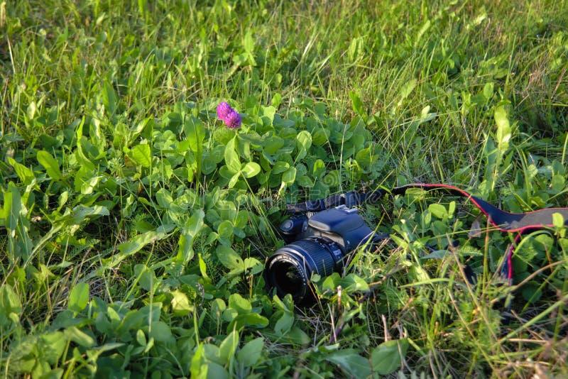 A black digital SLR camera lies on the grass close-up. stock photo