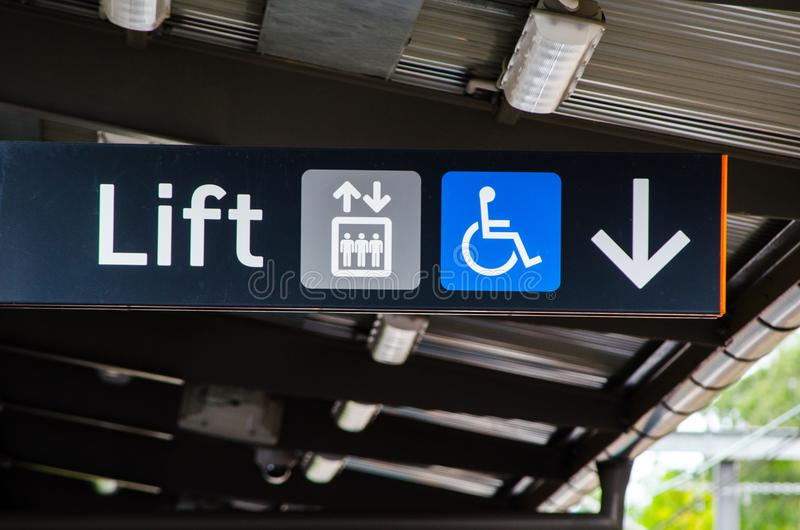 Black Direction sign pointing to the lift with disabled access. stock photo