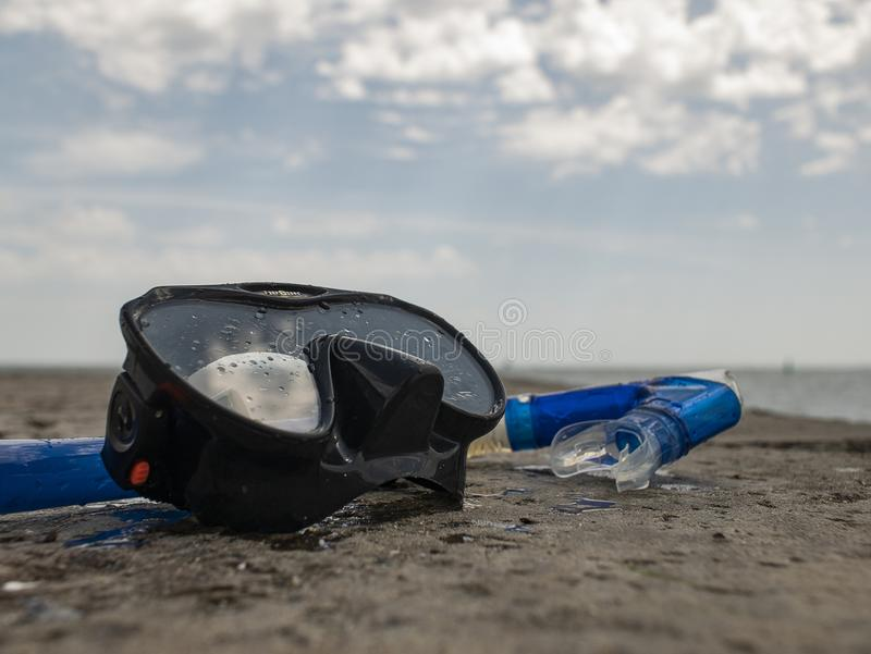 Black diving mask and snorkel on a concrete pier against the background of blue sky and clouds stock images