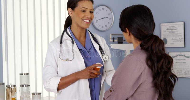 Black doctor explaining prescription medicine to patient. Black doctor explaining prescription medicine to female patient stock photos