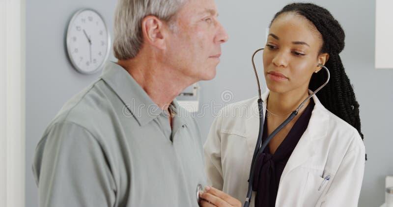 Black doctor listening to senior breathing.  stock image