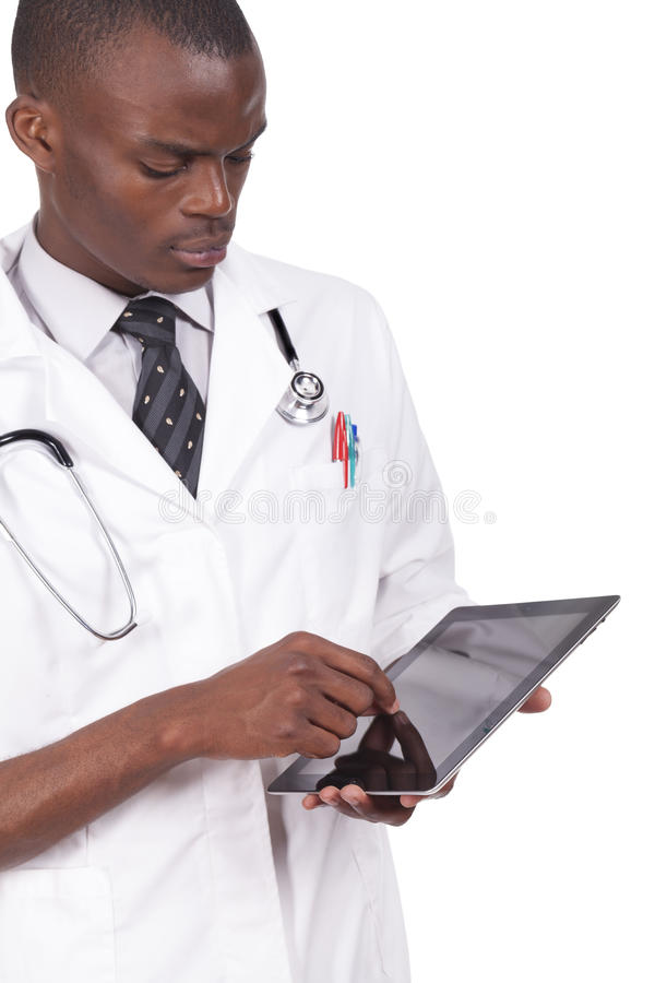 Black doctor looking at tablet. Young black doctor looking at tablet stock image