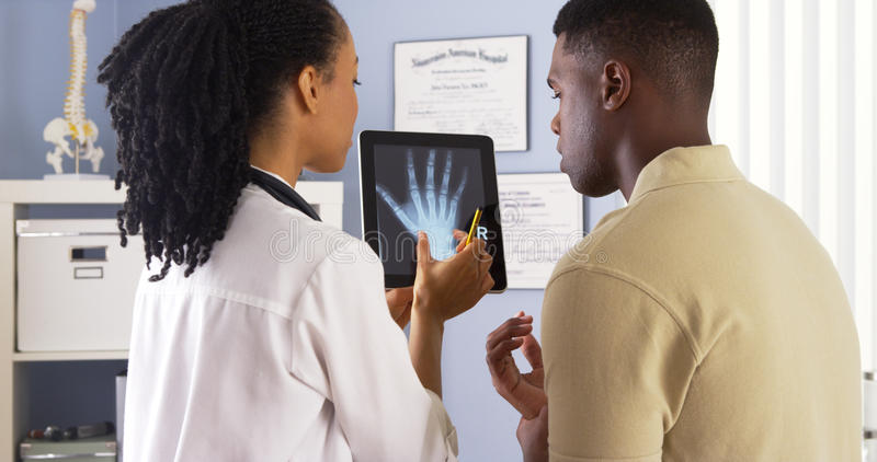 Black doctor sharing hand x ray with patient on tablet. Black female doctor sharing hand x ray with patient on tablet stock image