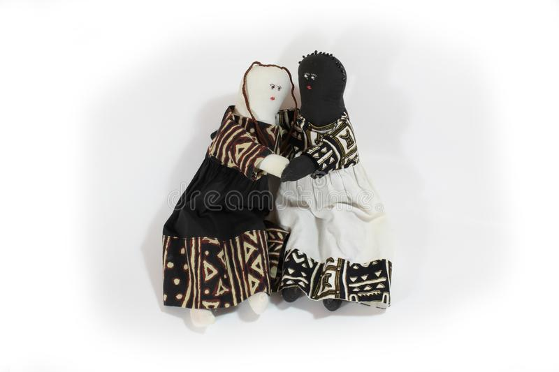 Black doll and white doll embrace concept forgiveness, reconciliation stock photos