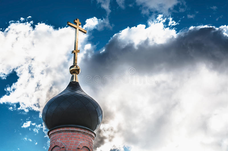 Black dome of the Church with a golden cross on the sky background with white clouds. tower of the old red brick in the light of t stock photography