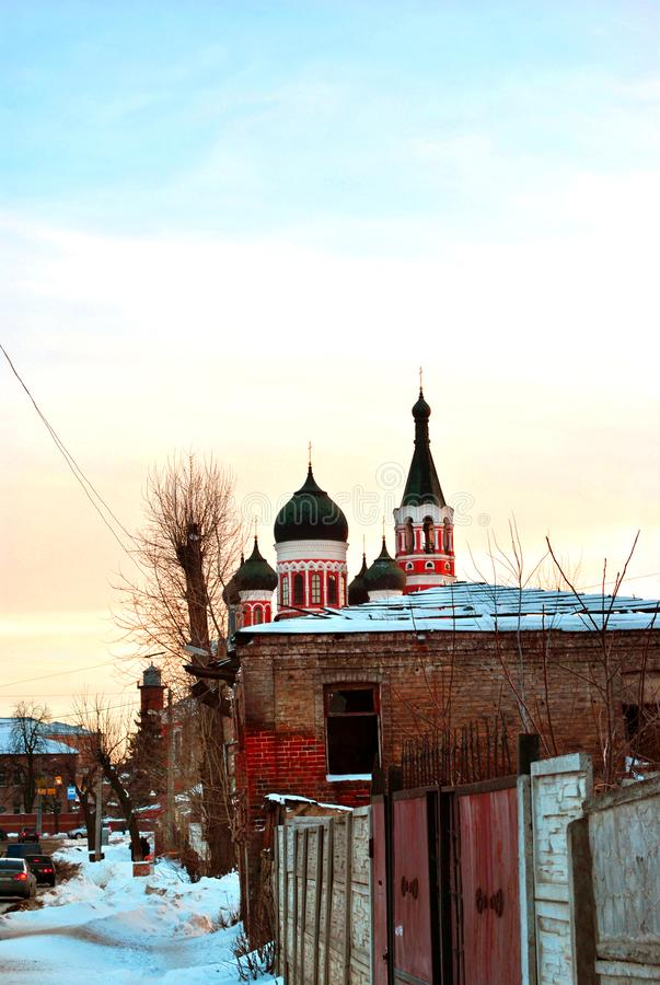 Black domes with crosses on top of orthodox church of red and white brick in winter evening landscape of residential. District along road with snow hills royalty free stock photos