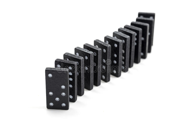 Black dominos in a row isolated on a white background royalty free stock photo