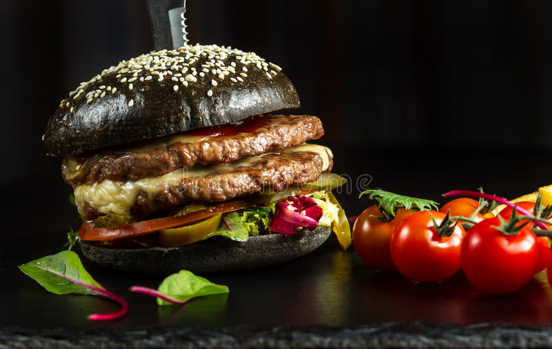 Black double hamburger made from beef, with jalapeno pepper. Next a sprig of cherry tomatoes. Close up stock images