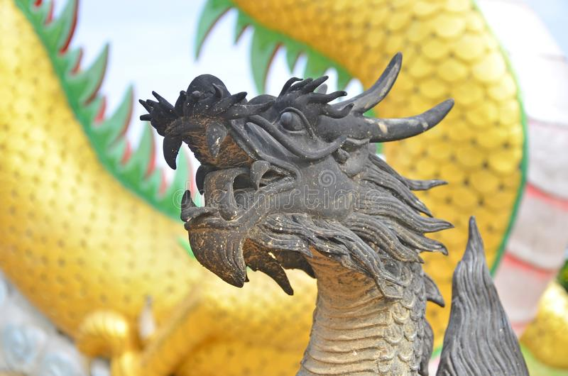 Black dragon sculpture with yellow body background royalty free stock photography