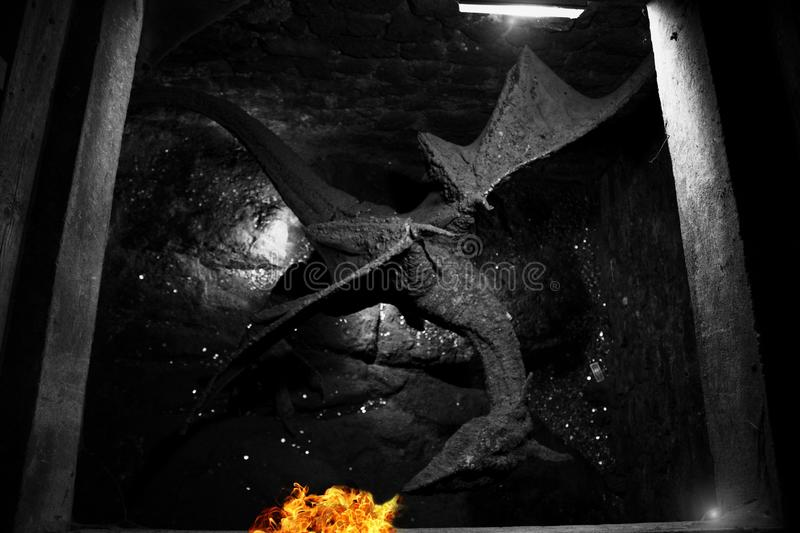 A black dragon spits fire in the basement of an old castle. stock photo