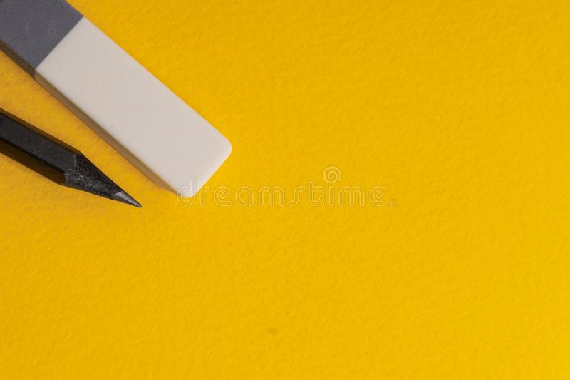 Black drawing lead pencil and eraser on a yellow background. Copyspace. Close, bright, symbol, metal, board, empty, blank, light, design, reflection, shadow royalty free stock photo