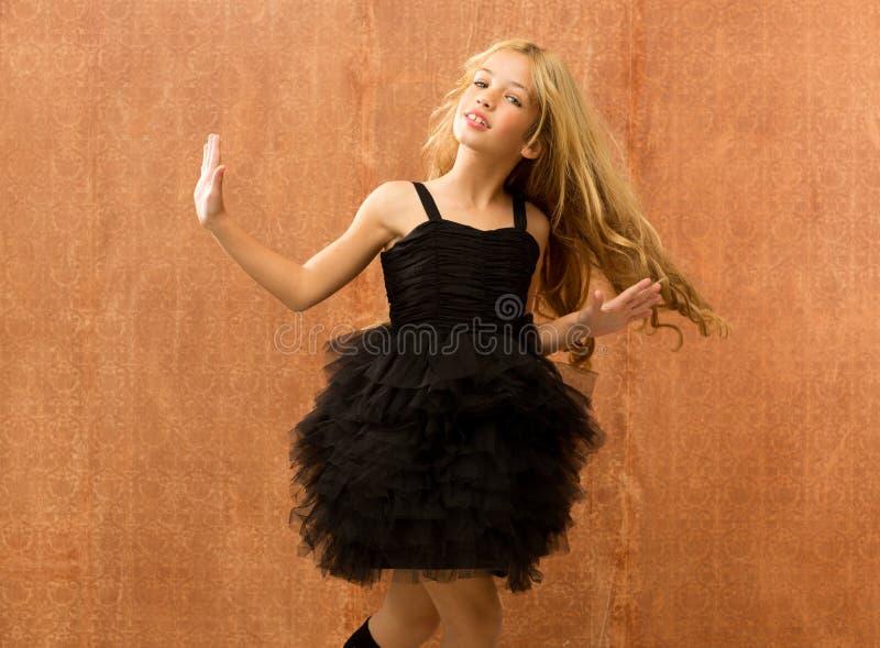 Black dress kid girl dancing and twisting vintage royalty free stock photo