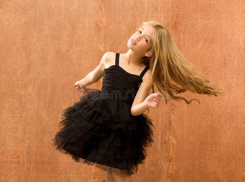 Black dress kid girl dancing and twisting vintage stock photography