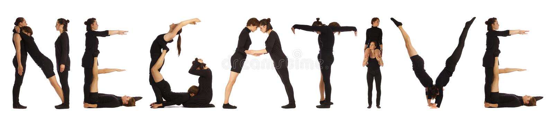 Black dressed people forming NEGATIVE word stock image