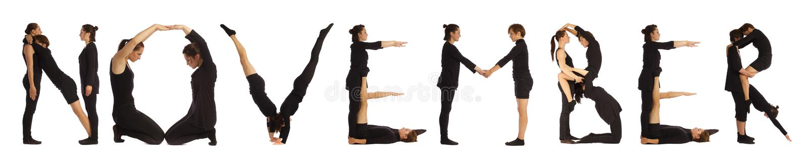 Black dressed people forming NOVEMBER word. Over white background stock photo