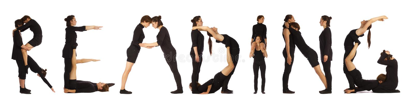 Black dressed people forming READING word stock photos