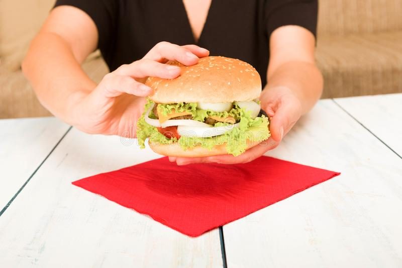 Black dressed woman holding a hamburger stock images