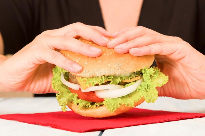 Black dressed woman holding a hamburger royalty free stock images