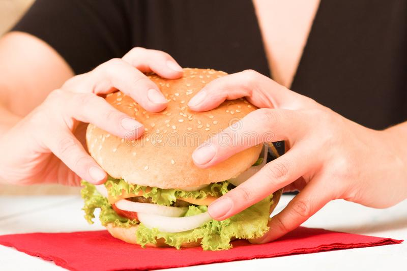 Black dressed woman holding a hamburger royalty free stock image