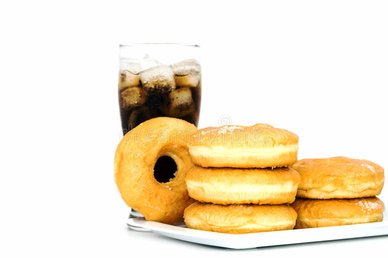 Black drink (cola) and donuts and sugar over lettuce over white. Background stock image