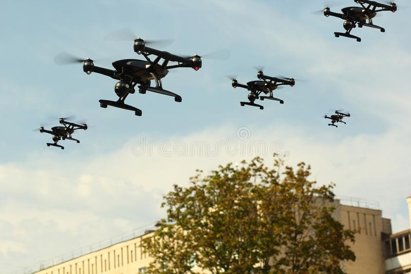 Black drone army flying in the city stock photos